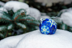 Blue Christmas Ball on snow. Blue Christmas Ball on white snow in winter . Green christmas tree background Stock Photo