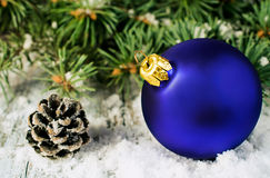 Blue Christmas ball and spruce branches in the snow Stock Photos