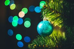 Blue Christmas ball on the spruce Christmas tree with multicolored bokeh round garland lights background. Christmas New Year holiday decoration tree ball garland stock photography