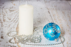 Blue Christmas ball, white candle and beads Royalty Free Stock Photo