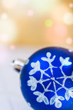 Blue Christmas ball with white snow flake ornament golden background with colorful confetti flare lights, copy space. Greeting card Stock Photos