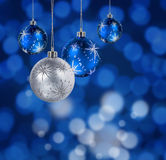 Blue christmas balls. Blue and silver Christmas balls hanging against blue light spots background royalty free stock image