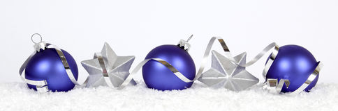 Blue christmas balls. Blue baubles and silver stars on the snow Royalty Free Stock Photo