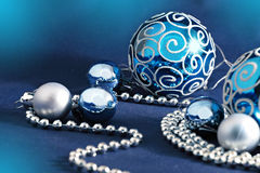 Blue Christmas balls and beads. Blue Christmas balls and silver small balls and string of pearls against blue background. Shallow depth. Horizontal position royalty free stock photo