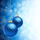 Blue Christmas Balls on a defocused flare Background. A Blue defocused Christmas background, with two blue striped christmas balls decorated with snowflakes Royalty Free Stock Image