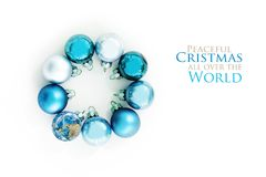 Blue Christmas balls and an earth globe in a circle, isolated wi. Th shadows on a white background, greeting card with text Peaceful Christmas all over the World royalty free stock image
