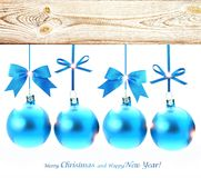 Blue Christmas balls hanging from the wooden surface isolated. Blue Christmas balls decorated with bows and lights on a white background. There is a place for Stock Photography