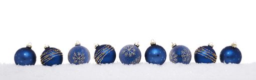 Blue christmas balls in a row isolated on snow stock photo