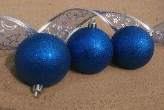 blue christmas balls in sand Royalty Free Stock Image