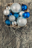 Blue Christmas balls and silver, beads lie in a wooden basket to Royalty Free Stock Photography