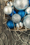 Blue Christmas balls and silver, beads lie in a wooden basket to Royalty Free Stock Photo