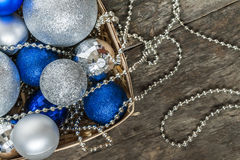Blue Christmas balls and silver, beads lie in a wooden basket to Stock Images