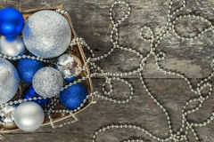 Blue Christmas balls and silver, beads lie in a wooden basket to Royalty Free Stock Photos