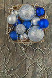 Blue Christmas balls and silver, beads lie in a wooden basket to Stock Photography