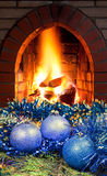 Blue Christmas balls on spruce tree and fireplace Stock Photo