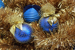 Blue christmas balls on a tinsel Stock Photos