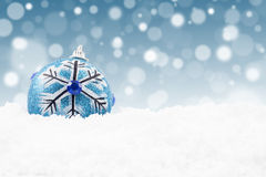 Blue christmas bauble. On the snow with christmas lights background Royalty Free Stock Photography