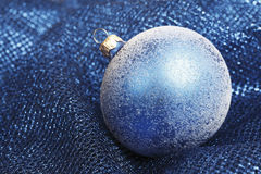 Blue christmas bauble on blue blanket Stock Images