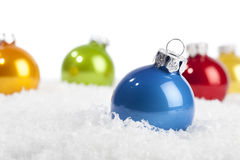 Blue Christmas bauble in decorative snow. One blue Christmas ball on a table with artificial snow, other baubles in the background Stock Image