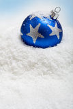 Blue christmas bauble in the snow. With copy space Stock Photos