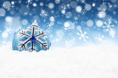 Blue Christmas bauble under snowflakes Royalty Free Stock Photo