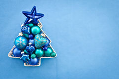 Blue christmas baubles. Arranged in a tree shape Royalty Free Stock Photos
