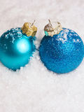 Blue Christmas baubles on snow Stock Images