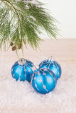Blue Christmas baubles in snowflakes and pine tree branch Stock Photography
