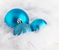 Blue Christmas baubles on soft white feathers Stock Image