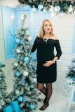 Blue Christmas concept. Happy smiling pregnant woman with red lipstick and blonde hair is touching her tummy near the. Decorated Christmas tree at home Royalty Free Stock Images
