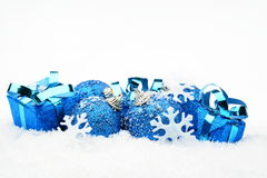 Blue christmas decoration on snow. Decoration of blue christmas baubles and gifts on snow white background Stock Photography