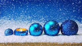 Blue Christmas decoration and snowfall. Blue christmas balls isolated.Advent candle and blue Christmas balls .Blue Christmas decoration and snowfall stock footage