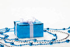 Blue Christmas gift box with shiny silver ribbon and beads on white background Royalty Free Stock Photography
