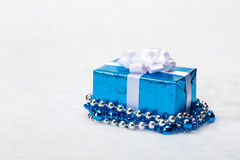 Blue Christmas gift box with shiny silver ribbon and beads on white background Stock Image