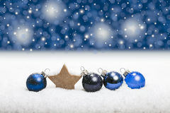 Blue christmas gift certificate. Row of blue christmas balls and wooden star lying in the snow in front of red background with glittering lights kitschy bokeh Stock Image