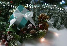 Blue Christmas gift nestled in decorations. And lights Stock Images