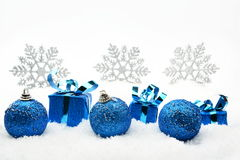 Blue christmas gifts and baubles with snowflakes on snow Royalty Free Stock Photography