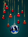 Blue christmas glittery ball. Closeup of hanging christmas blue globe with glittery decorations, with golden threads on blue gradient background with blurred red royalty free stock photography