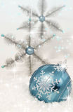 Blue Christmas Ornament. A turquoise blue Christmas ornament decorated with white snowflake resting in snow. Turquoise and silver snowflake ornaments softly Stock Photo