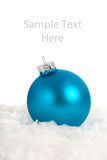 A blue Christmas ornament/bauble with copy space. A shiny blue Christmas ornament/bauble on snow with copy space Royalty Free Stock Photography