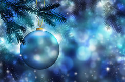 Blue Christmas ornament. A blue Christmas ornament in pine branches with a blue background. Christmas season concept royalty free stock image