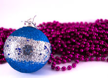 Blue Christmas ornament with purple mardi gras beads. Blue onrament with purple mardi gras background royalty free stock photo
