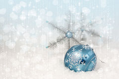 Blue Christmas Ornament Snowflakes. A vivid blue Christmas ornament resting in snow with silver snowflakes in background royalty free stock photography