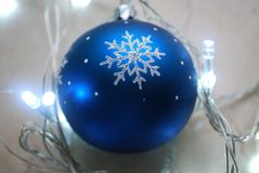 Blue christmas ornament surrounded by garland in cold tones. Royalty Free Stock Images