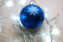 Blue christmas ornament surrounded by garland in cold tones. Royalty Free Stock Photos