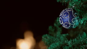 Blue Christmas ornament on tree with a black background