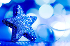 Blue Christmas star and glitter. On the blue background Stock Images