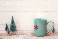 Blue Christmas tea mug with red snowflake and miniature firs on. Wooden table. Copy space Royalty Free Stock Photography