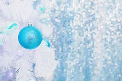 Blue Christmas toy hanging on a white spruce with snow. stock photo