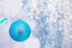 Blue Christmas toy hanging on a white spruce with snow. royalty free stock images